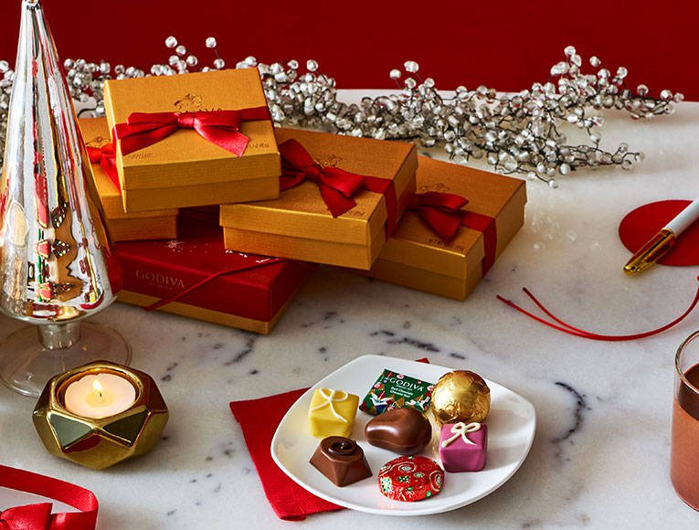 Stacked gold favor gift boxes with red ribbon next to plate of seasonal chocolate pieces