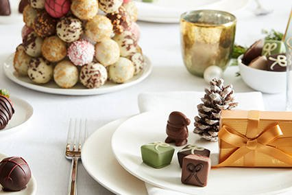 Blue and green ribbon alongside plate of chocolate pieces