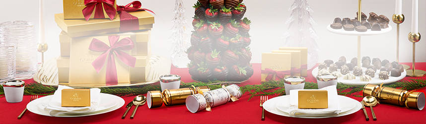 Gold Gift boxes, chocolate strawberries, pedestal of chocolates and favors on plates