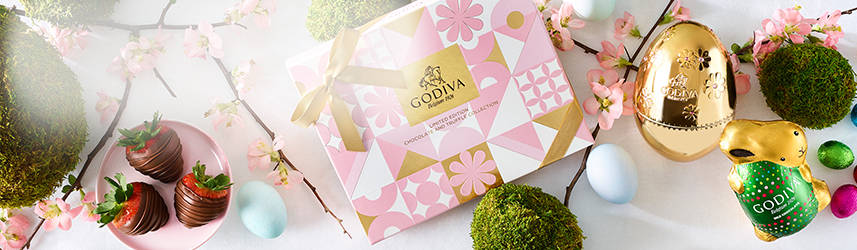 Spring gift box beside chocolate strawberries and foil eggs