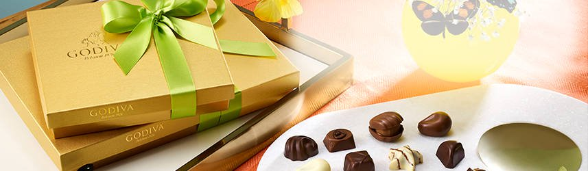 Gold gift boxes with green ribbon along plate of chocolate